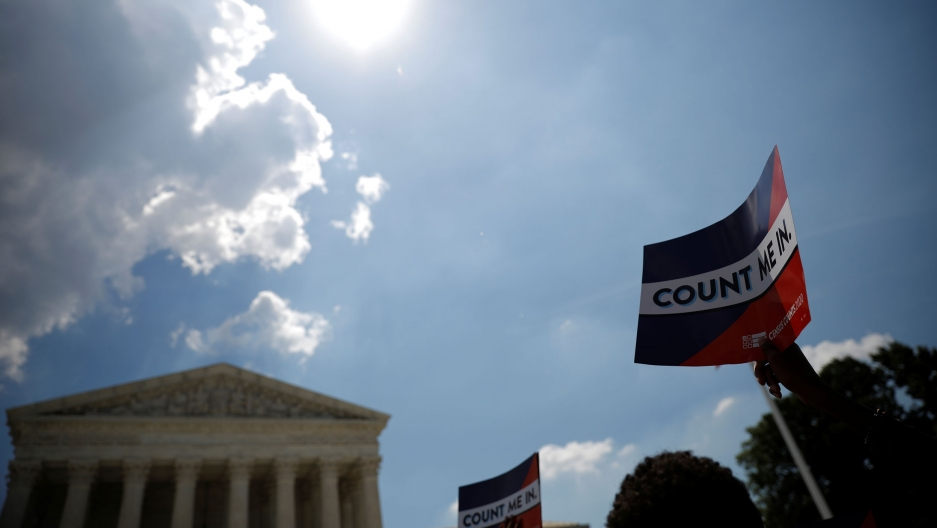 """The facade of the Supreme Court building is seen in the background with a placard raised in the nearground with the words """"Count Me In"""" printed on it."""