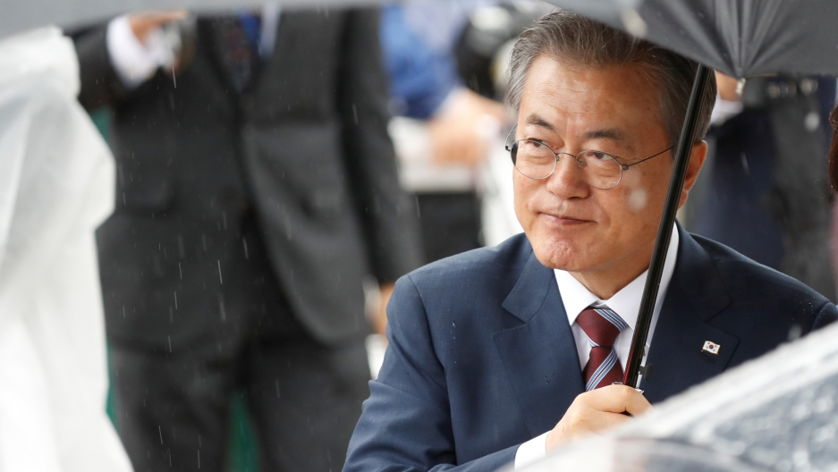 South Korea's Moon Jae-in holds an umbrella over his head