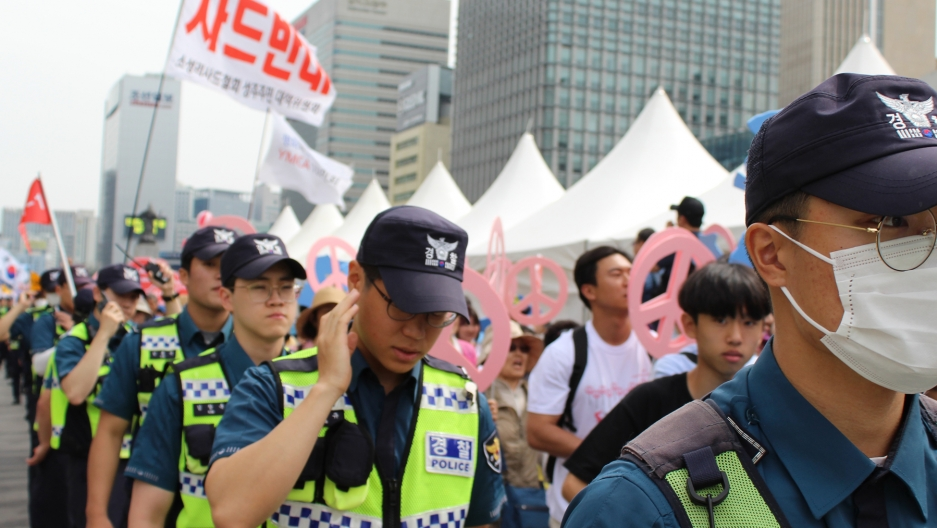 Police control crowd in protest with signs with Korean letters.