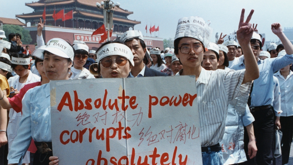 Protesters in Tiananmen Square hold up a sign that says absolute power corrupts absolutely.