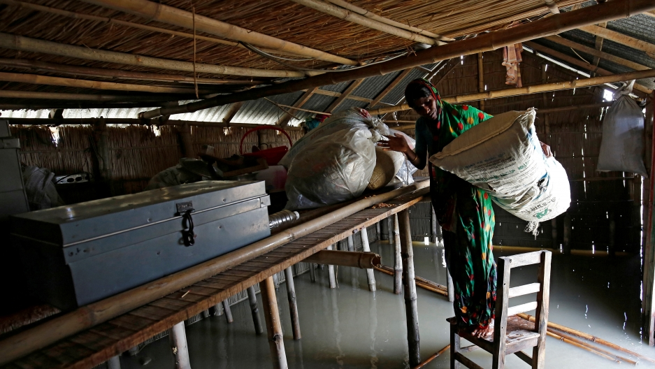 A woman moves her things onto a table in a flooded home.