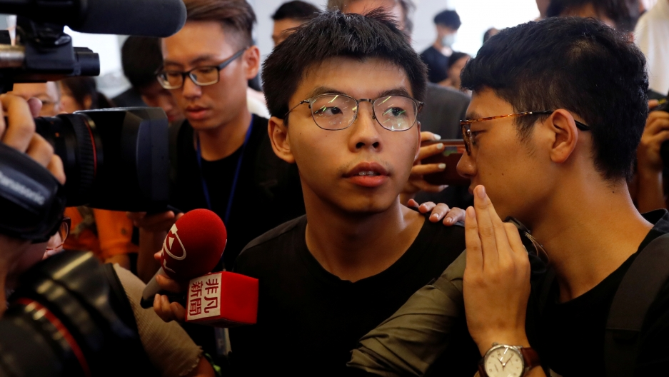 Cameras and people surround Joshua Wong as he speaks to the media.