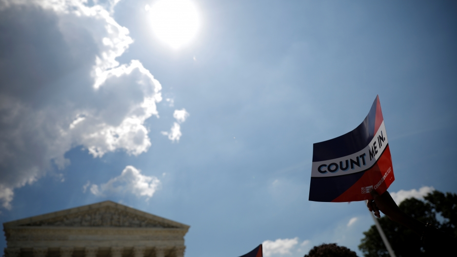 "A sign that says ""Count Me In"" with the US Supreme Court building in the background"