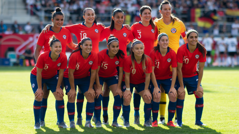 Women's soccer team posing for group shot in red uniforms.