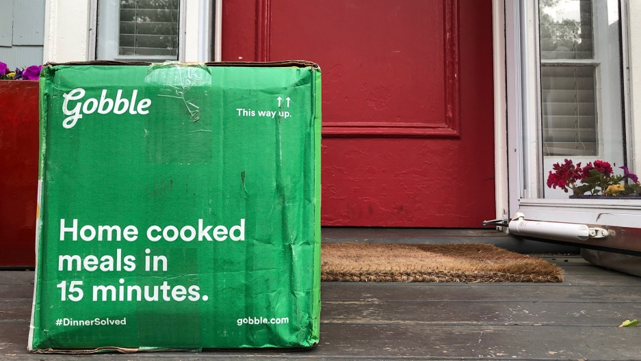 A green cardboard box sits on a door stoop.