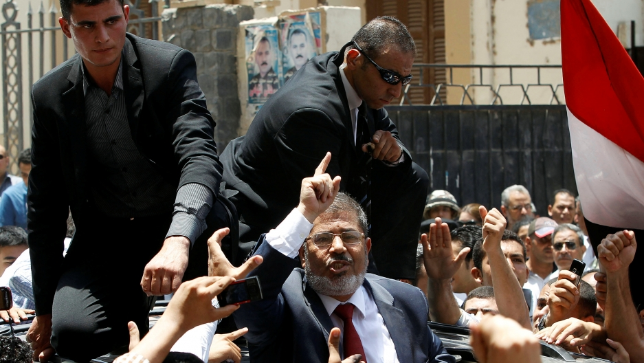 Mohammed Morsi, former president of Egypt, waved to his supporters after casting his vote at a polling station in a school in Al-Sharqya, 37 miles northeast of Cairo, on June 16, 2012.