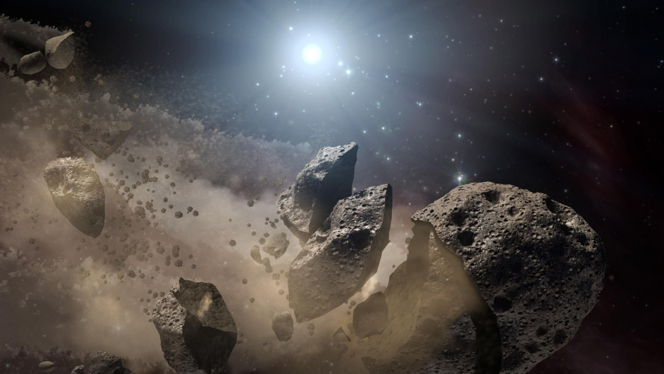 An asteroid breaking into little pieces in space.