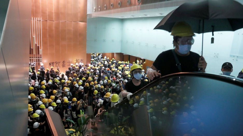 Hundreds of protesters are seen in the lobby of Hong Kong's legislative building wearing yellow hard hats and riding up an elevator.
