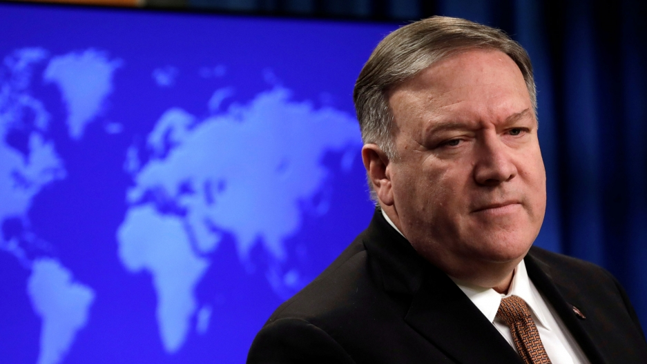 US Secretary of State Mike Pompeo is shown looking to his right and wearing a dark suit with a blue map of the globe behind him.