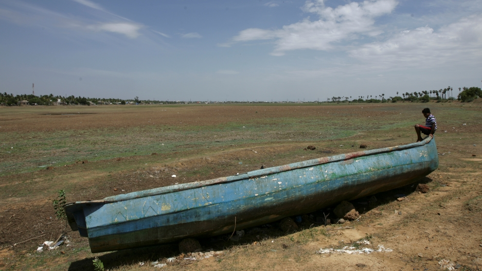 A man sits on a fishing boat stranded on the bed of dried-up lake in Thiruninravur, India, June 29, 2019.