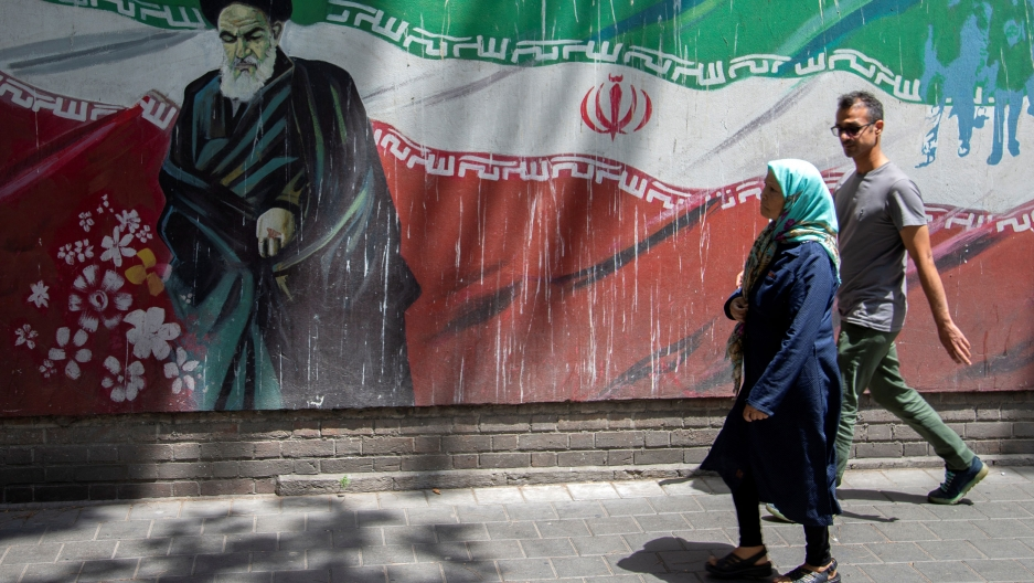 A woman wearing a shawl and a man wearing glasses are shown walking past a mural of Ayatollah Ruhollah Khomeini in front of an Iranian flag.