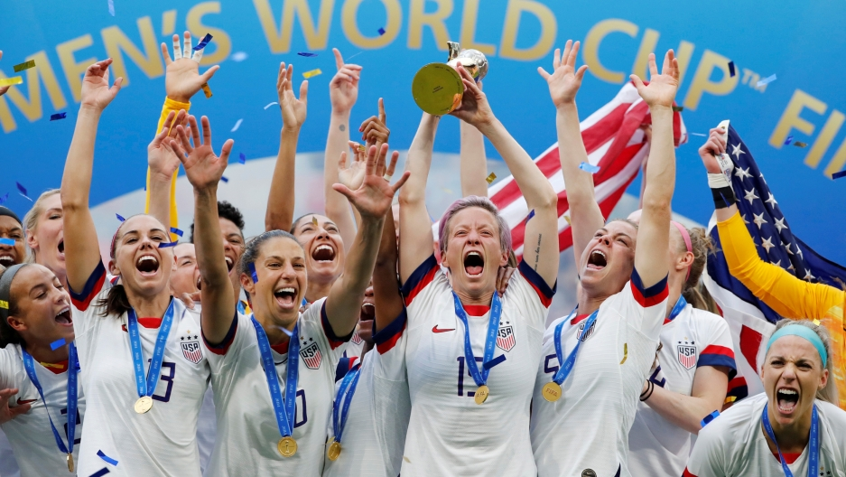 The US women's soccer team celebrates with the world cup trophy