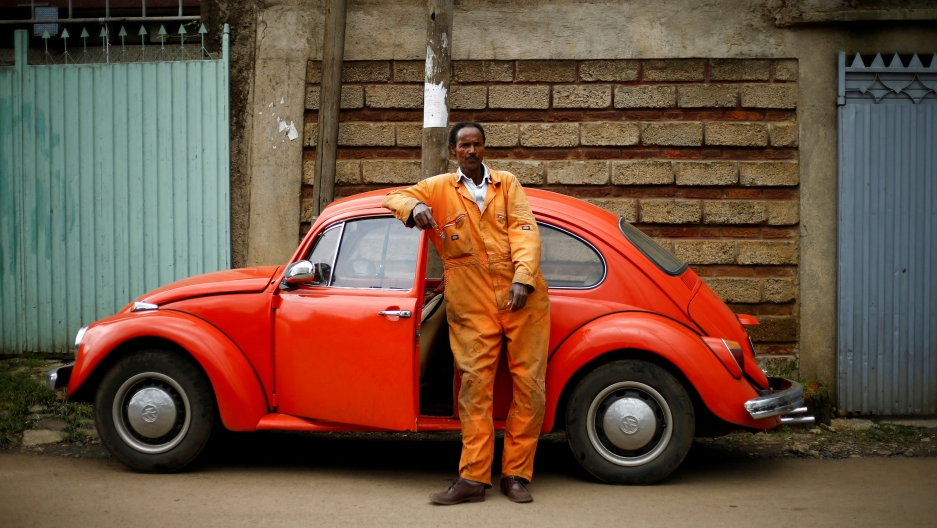 A man in an orange jump suit leans his arm on a red 1965 model Volkswagen Beetle car.