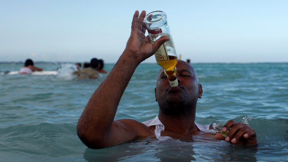 a man in the ocean drinks straight whisky from the bottle