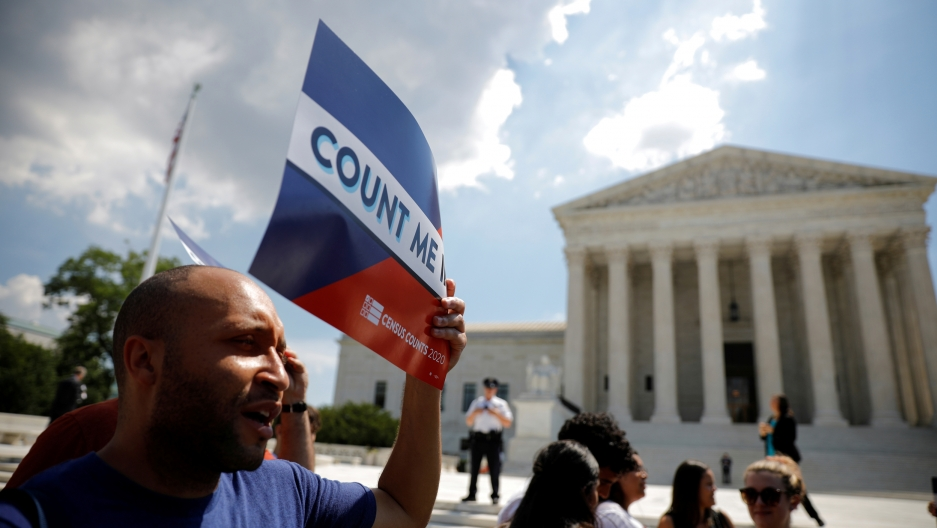 "A man stands in front of the US Supreme Court building holding a sign that says ""Count me"""