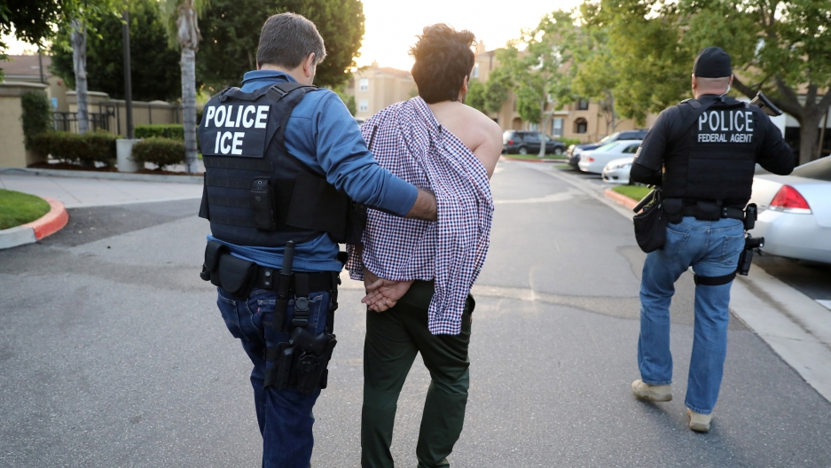 A man wearing a police vest reading POLICE ICE leads another man in handcuffs away. The handcuffed man has an open shirt draped over his shoulders. To the right is another man with a vest that says POLICE federal agent.