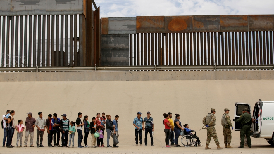 A line of migrants that includes young and older people along with a person in a wheelchair are shown standing next to the large border fence.