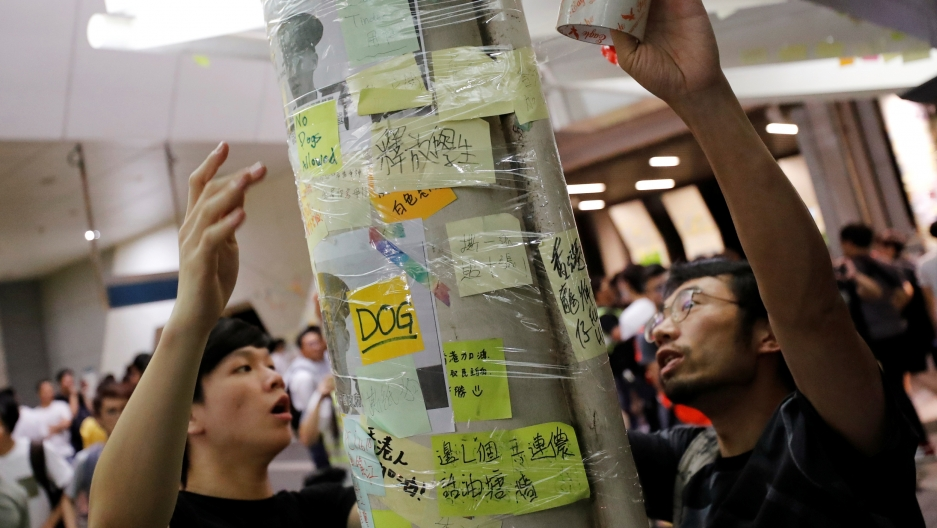"Two people wrap tape around a column covered in post-it notes to protect the ""Lennon Wall"""
