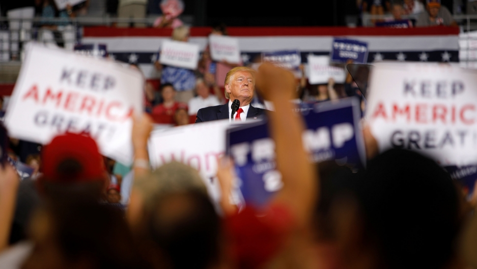 A large crowd of people are shown in soft focus holding placards with Donald Trump in center frame in focus.