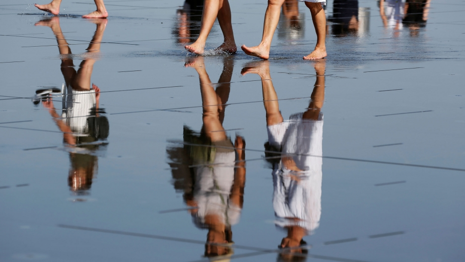 The reflection of several women are shown in water with just the bottom part of their legs shown at the top of the photograph.