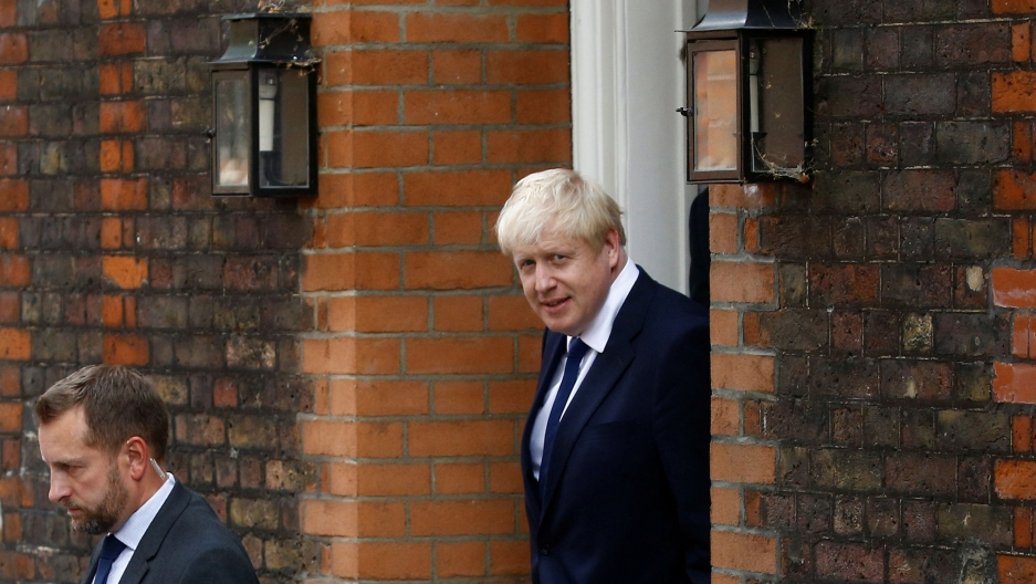Boris Johnson is shown walking through a brick doorway wearing a blue suit.