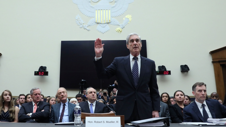 Former Special Counsel Robert Mueller is shown with his right hand raised with a crowd of people seated behind him.