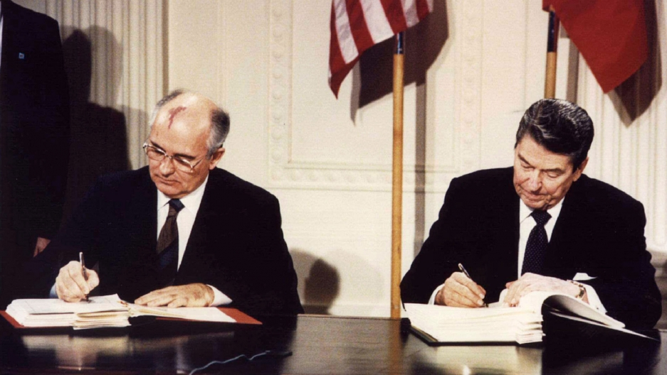 Two men sit at a desk and sign a paper