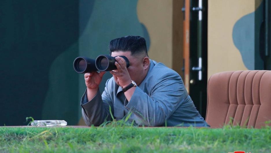north korean leader Kim Jung-un peers through binoculars