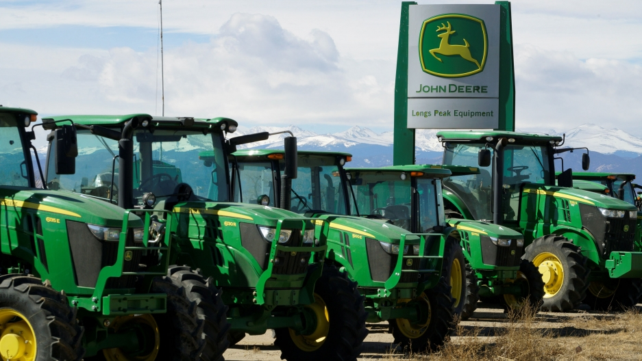 Several green John Deere trackers are shown in a row with a sign for the company in the background.