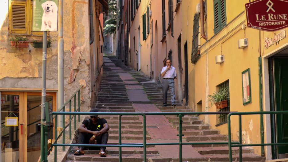 an asylum-seeker in Italy sits at the bottom of some stairs in Genoa