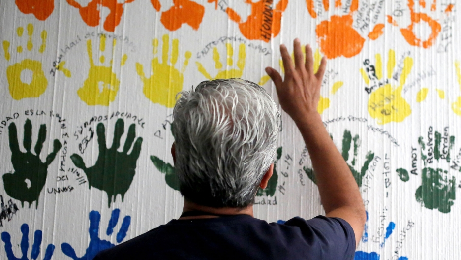 a man holds up his right hand in front of a wall of fingerpaint-hands