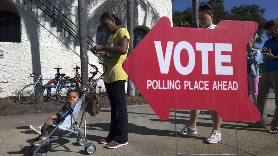 A sign saying vote in the foreground with people and a child in a stroller in the foreground