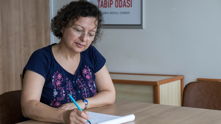 A woman sits at a table and writes on a notepad.