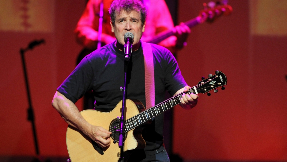 Singer Johnny Clegg performs on stage.