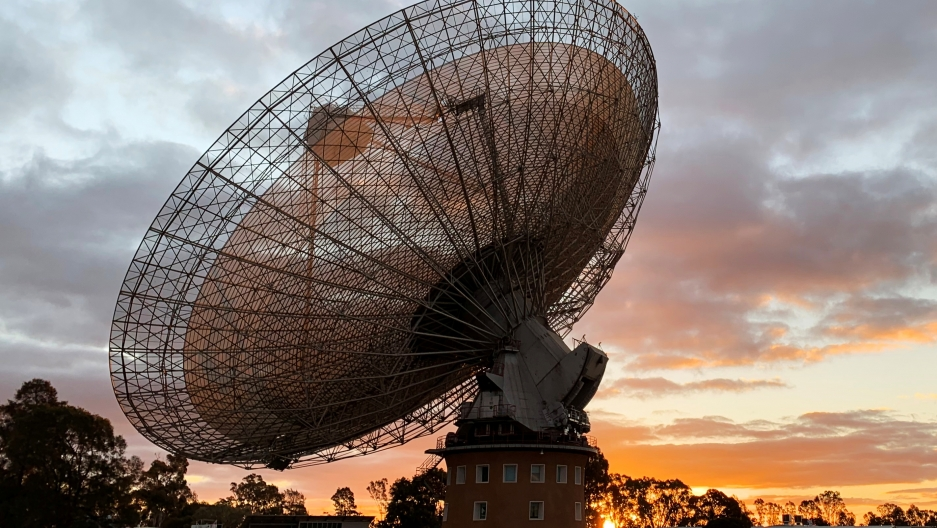 A radio telescope dish at sunset.