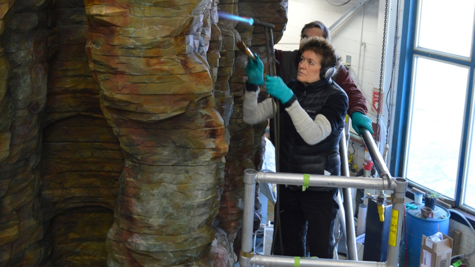 "Ursula von Rydingsvard climbs a ladder to work on her sculpture ""Bronze Bowl with Lace,"" 2013."