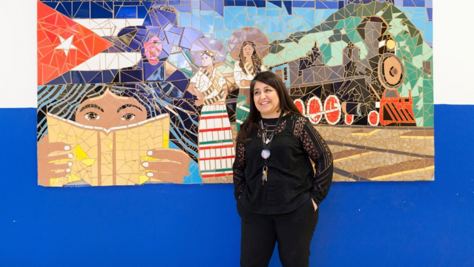 Woman in a black suit poses in front of a tile mural.