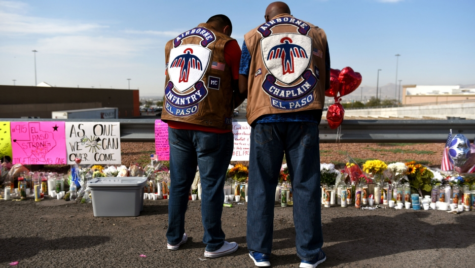 Two men bow their heads as they stand in front of an impromptu memorial for El Paso shooting victims