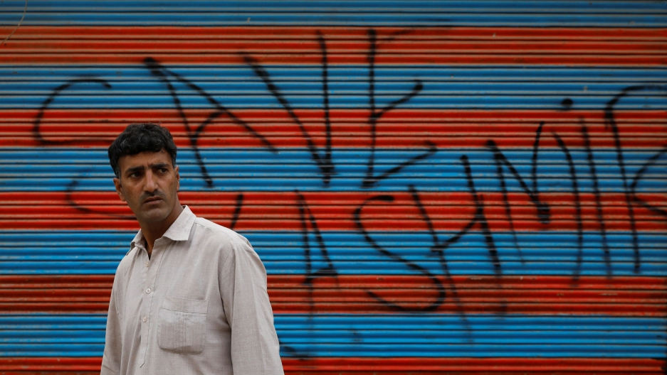 "A man walks in front of a wall spray painted with the words ""Save Kashmir"""