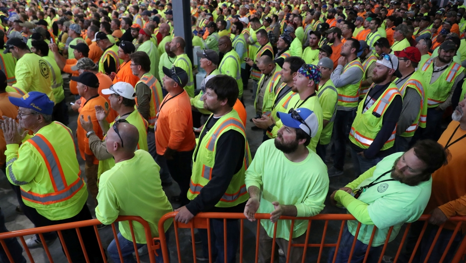 A crowd of workers in bright florescent colors stand and listen to a speaker