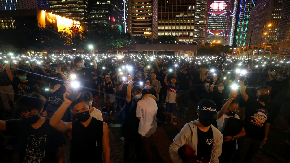 Crowds gather at night in a plaza in Hong Kong.