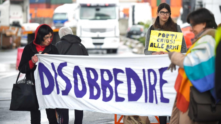 "People hold a handpainted banner that reads ""Disobbedire."""