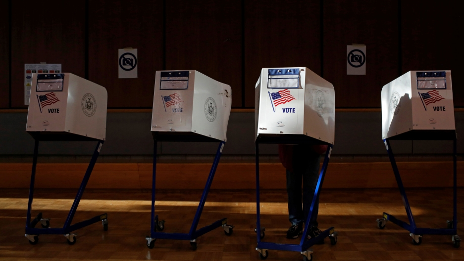 Four stand-alone voting booths are shown with US flags and the word 'vote' printed on the,
