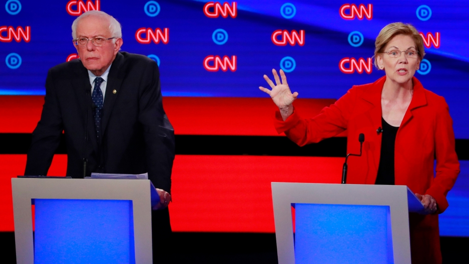 Bernie Sanders and Elizabeth Warren each stand at their podiums on the debate stage