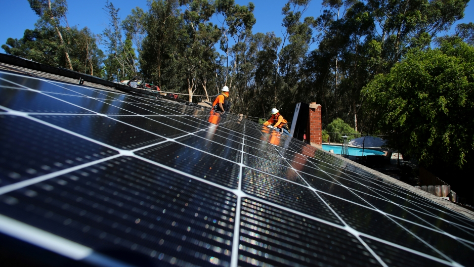 workers intsall solar panels on a rooftop in california