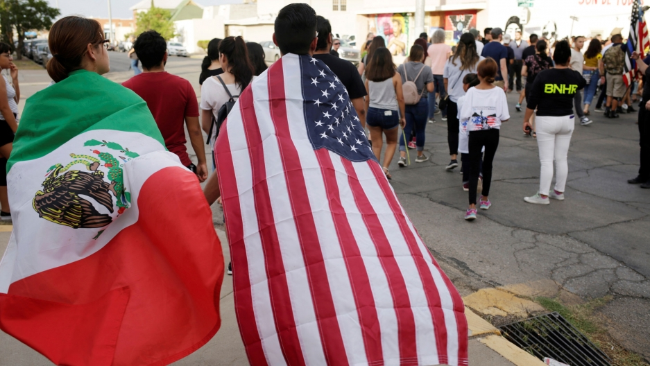 Two people are shown walking away from the camera with a Mexican flag and a US flag draped over their shoulders like capes.