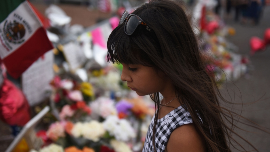 A young girl is shown in a checkered dress with long dark hair and sunglasses, standing in front of a memorial.
