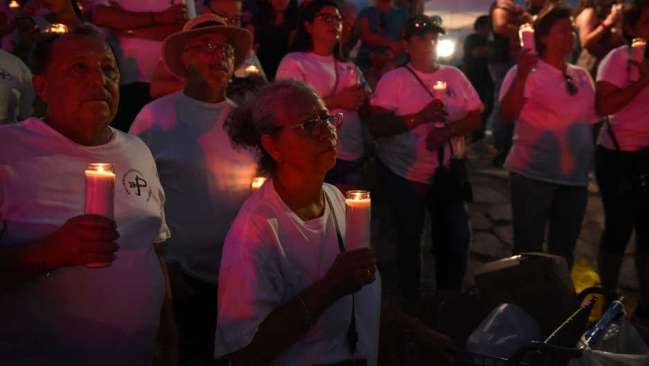 A group of people hold candles during a vigil at a memorial.