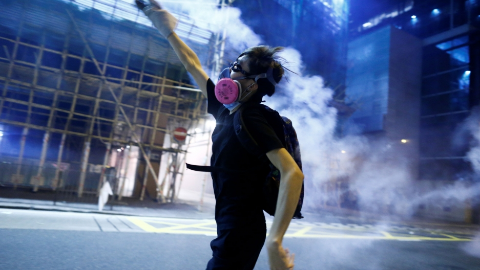 A protester throws a tear gas cartridge against a dark, blue background