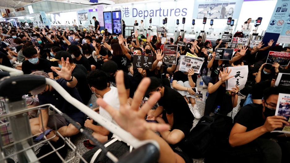 A crowd of demonstrators are shown with their hand in the air and hiding their face in Hong Kong Airport.